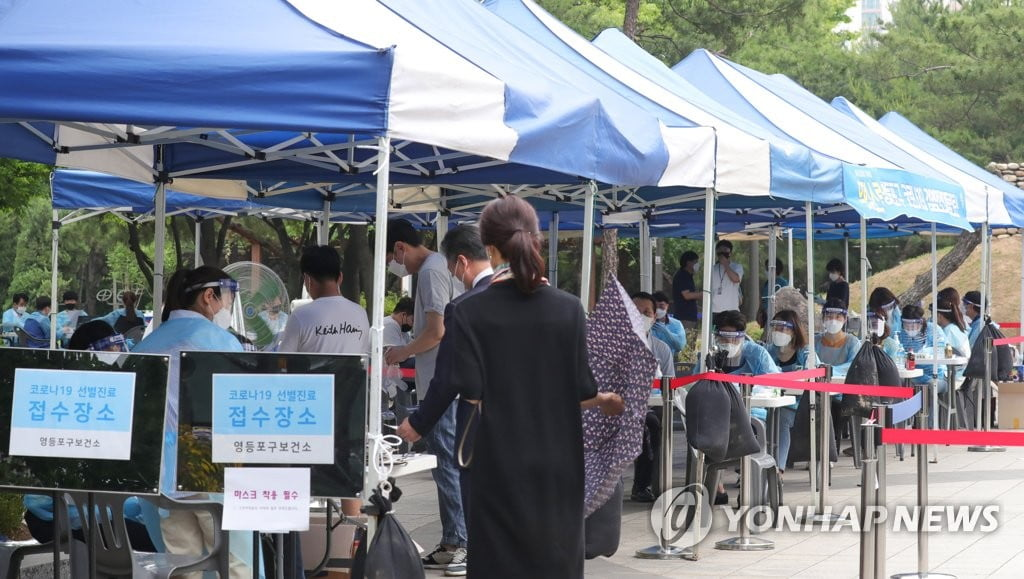 "Citizens line up to receive tests for the new coronavirus at a ""walk-through""-style testing site in the financial district of Yeouido in Seoul on May 31, 2020. (Yonhap)"