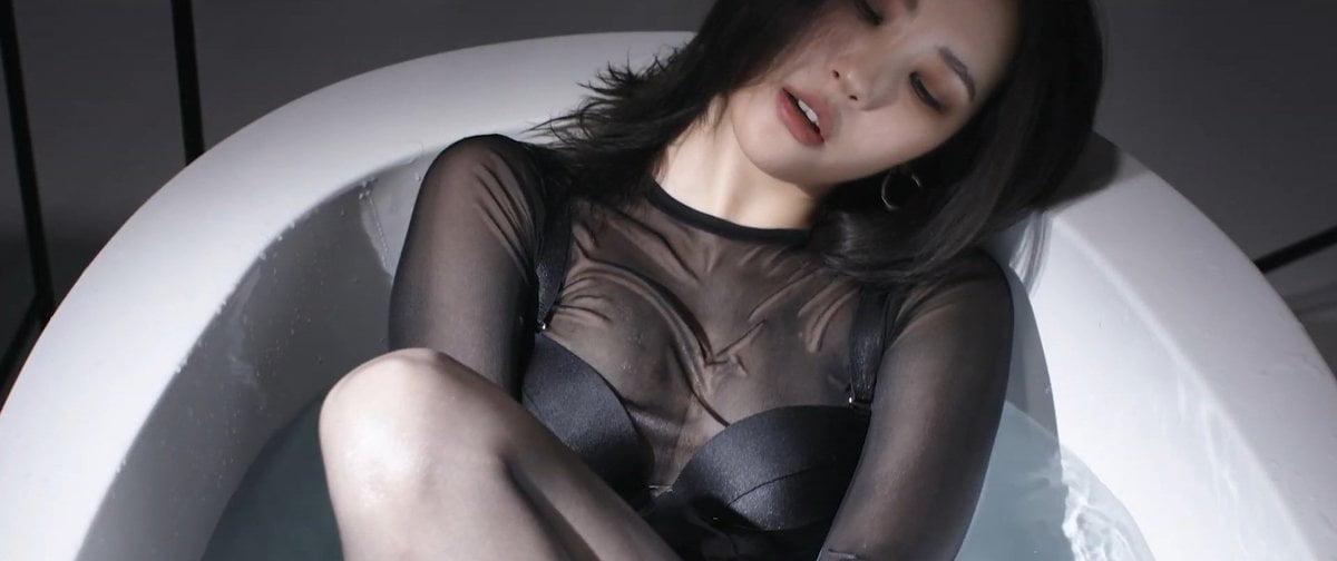 Cantora Sunmi em uma banheira, usando uma roupa preta, no clipe de  Borderline, que fala sobre sua vivência com o transtorno de personalidade borderline